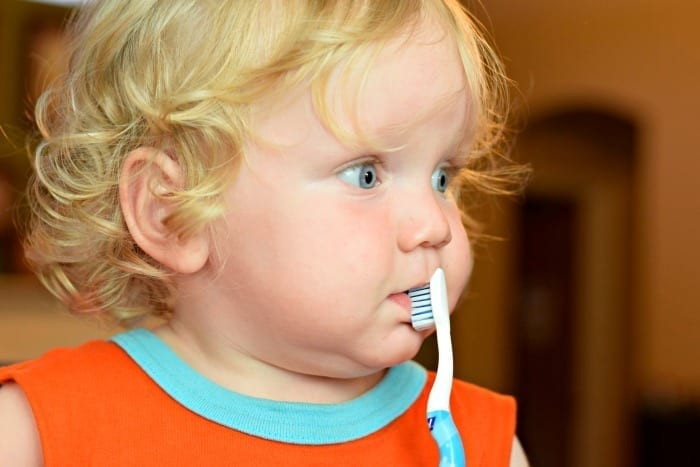 baby brushing with orajel toothbrush