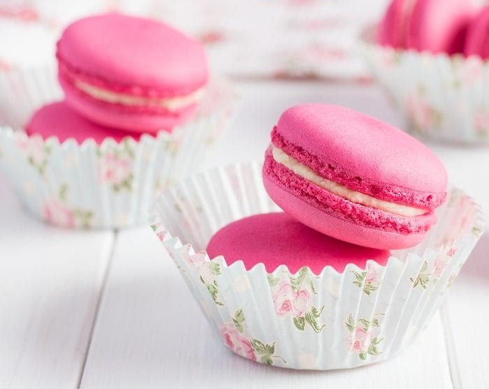 Pink bubblegum french macarons stacked inside a cupcake paper on a white background.