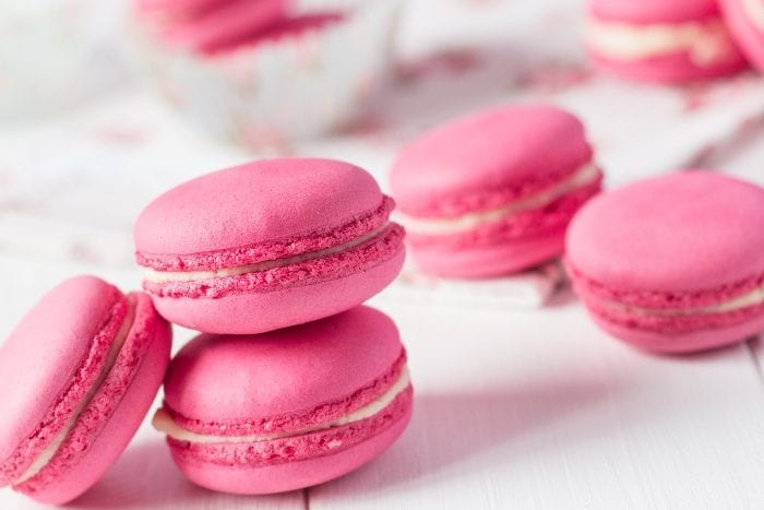 Pink French Bubblegum macaron cookies stacked together on a white background.
