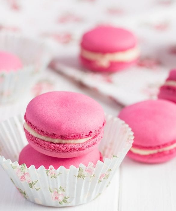 Pink bubblegum french macaron cookies stacked and sitting in a cupcake paper.