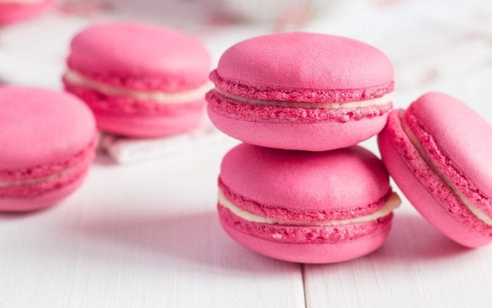 Pink french macaron cookies on a white background.