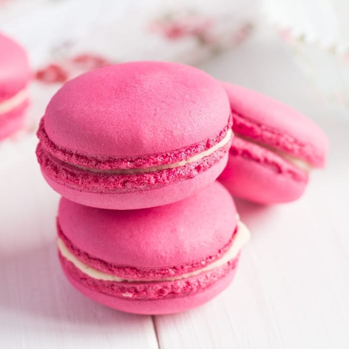 Pink Bubblegum flavored macaron cookies on a white background with white chocolate ganache filling.
