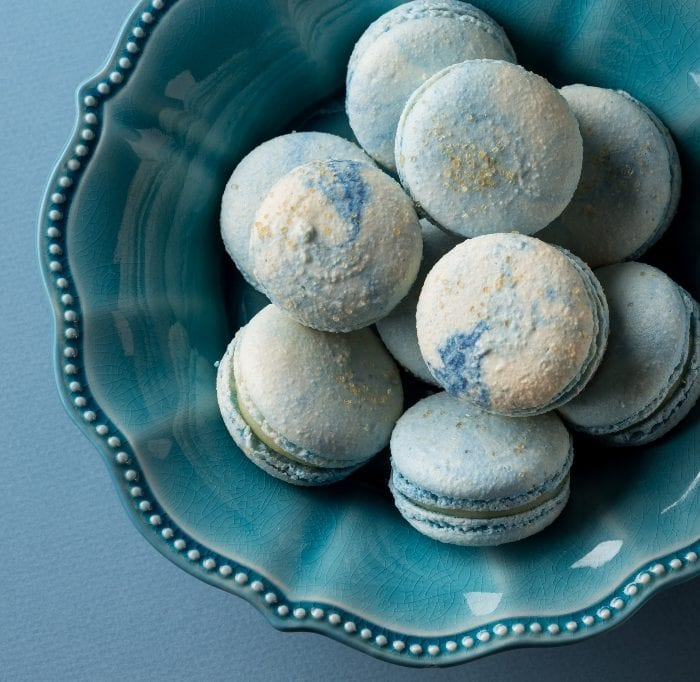 Blue Cotton Candy flavored French macaron cookies in a blue bowl on blue background.