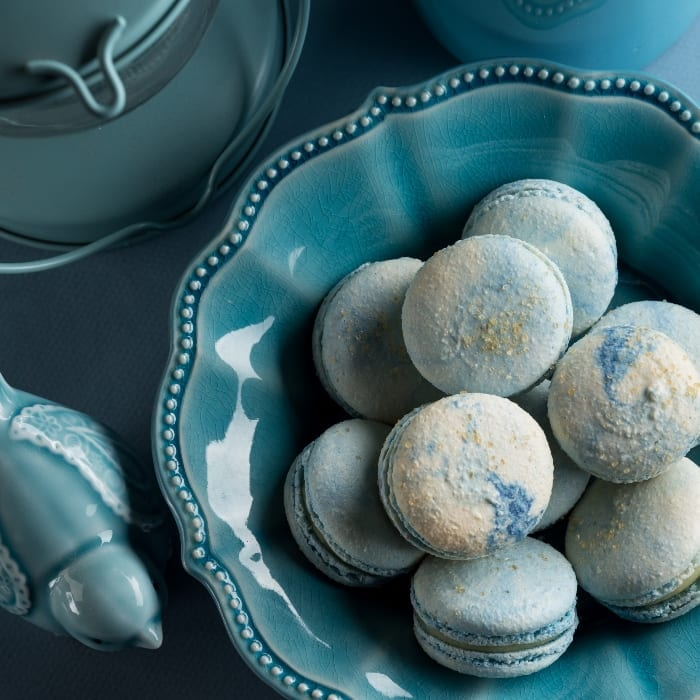 Top-down image of blue cotton candy french macaron cookies in a blue bowl next to a blue glass bird and blue candle lamp.