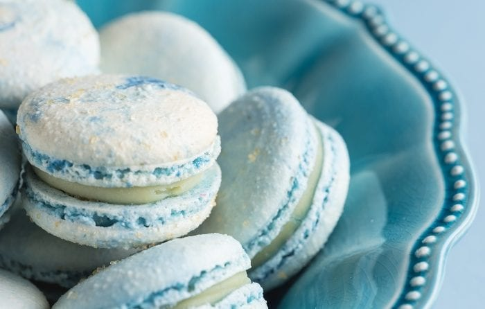 Close-up of blue cotton candy macarons in a blue bowl.