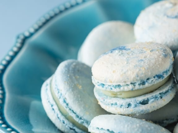 Closeup of cotton candy french macarons in a blue bowl.
