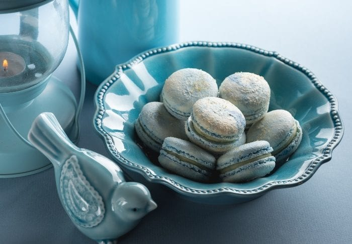 Blue bowl full of blue cotton candy flavored macaron cookies next to a blue glass bird and an old fashioned candle lamp with a blue pitcher in the background.