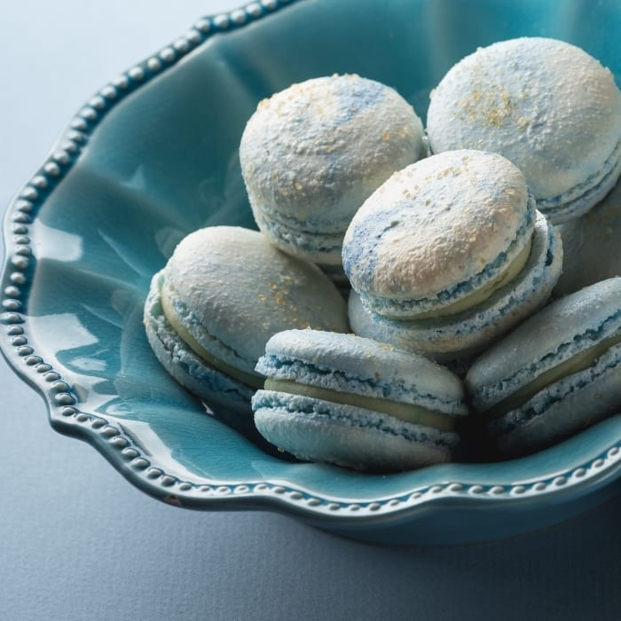 Blue bowl full of french macarons in blue color with cotton candy flavoring and a white chocolate ganache filling.