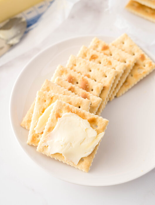 buttered saltine crackers on a plate